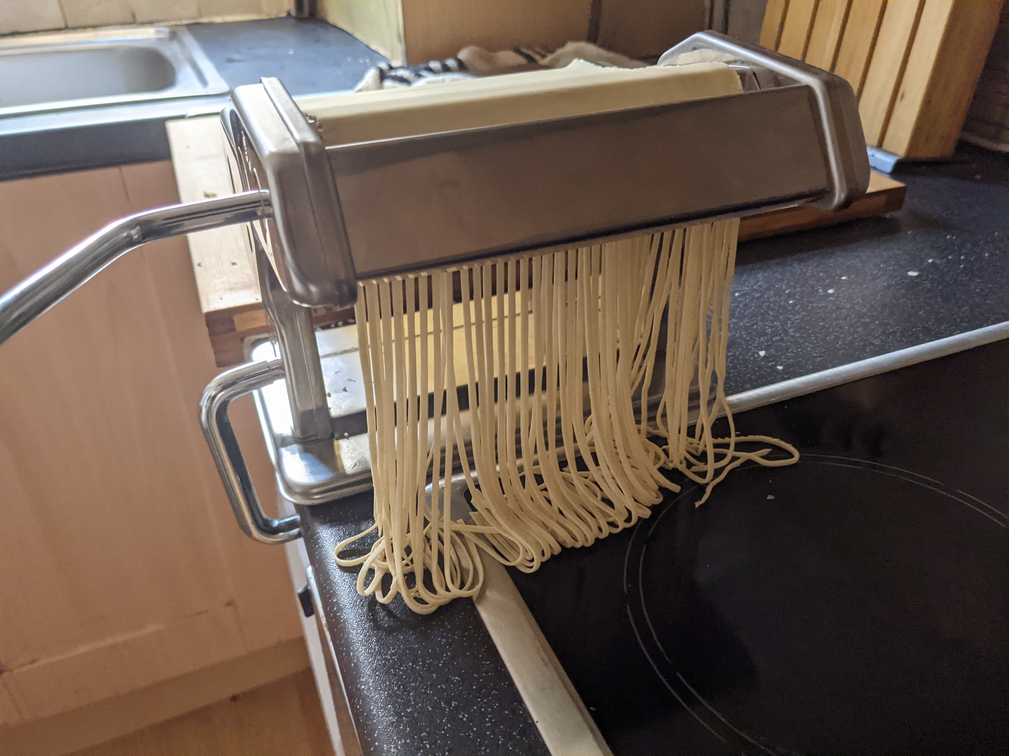 Noodles being cut with a pasta machine